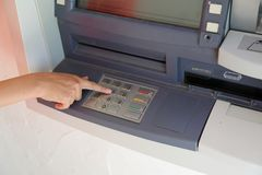 Hand type the secret code in the ATMs keyboard to pick up the mo. Hand of girl type the secret code in the ATM's keyboard to pick up the money Stock Image