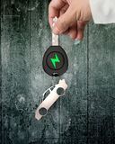 Hand give electric car key sports car sheet metal keyring. Green energy electric car and lightweight high strength speed concept. Businessman hand holding stock photography