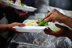 Hand give food to hands of a beggar royalty free stock images