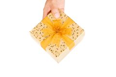 Hand give golden christmas gift box with golden bow Royalty Free Stock Photography
