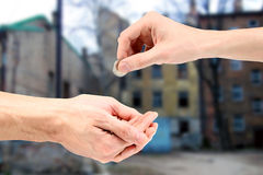 Hand gives coin to beggar Stock Image