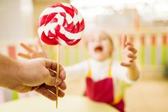 Hand gives handmade lollipop to happy little girl. Children in workshop at pastry shop. Holiday fun in candy store. Fresh cooked sugar caramel Stock Photography