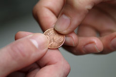 Hand giving 2 cents euro coin to other hand. Stock Image