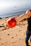 Hand giving apple at beach. Hand of young woman offering red apple at beach Stock Photography