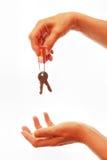 Hand giving away house keys. Human hand giving away house keys real estate Stock Photos