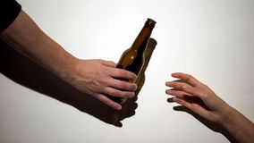 Hand giving beer bottle to alcohol addict with self-inflicted arm, harmful habit. Stock photo royalty free stock photos