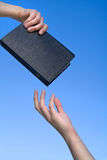 Hand Giving the Bible. To another person over blue sky Stock Photography