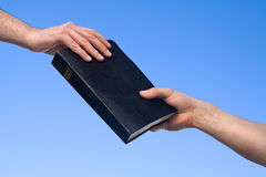 Hand Giving Bible. Hands holding the Bible over blue sky Royalty Free Stock Photography