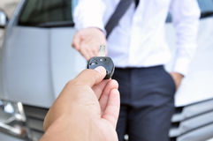 Hand giving a car key- car sale & rental service concept. Hand giving a car key to another man - car sale & rental service concept Royalty Free Stock Images