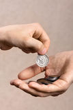 Hand giving a coin to another person Stock Images