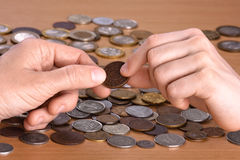 Hand giving a coin to hand of another person. Hand giving a coin to another person, closeup Stock Photo