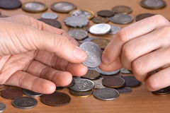 Hand giving a coin to hand of another person, closeup. Hand giving a coin to another person, closeup Stock Photography