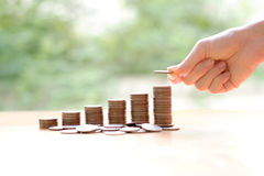 Hand giving coins into stack, business and finance Royalty Free Stock Photography
