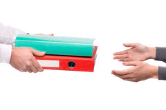 Hand giving folders to other person Stock Photography