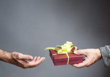 Hand giving a gift Stock Images