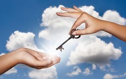 Hand giving key. A person's hand gives a large metal key to another person with a cloudy sky background Royalty Free Stock Photo