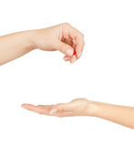 Hand giving medicine to other hand Stock Image