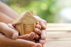 Hand is giving a model of a house to child`s hand stock images