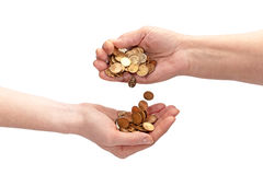 Hand Giving Money. An elderly woman's hand pouring coins into the hand of a young female. Isolated over white Royalty Free Stock Photography