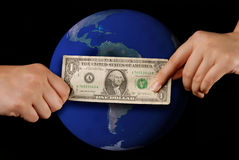 Hand giving money; earth. This stock photo shows the hand of one person giving money to another person.  Can illustrate concepts of giving, spending or commerce Royalty Free Stock Images
