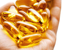 Hand is giving Omega 3 capsules on white background Royalty Free Stock Images