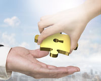 Hand giving one golden puzzle piece with keyhole Royalty Free Stock Photography