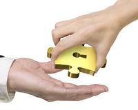 Hand giving one golden puzzle piece with keyhole Royalty Free Stock Image