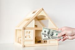 Hand giving one hundred us dollar banknotes. Wooden house model on background. Real estate investment.Bargain or deal concept.  royalty free stock photos