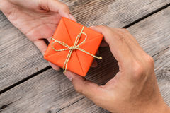 Hand Giving Orange Gift Box and Yellow Ribbon Royalty Free Stock Photos