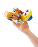Hand giving plate with cakes Stock Photography