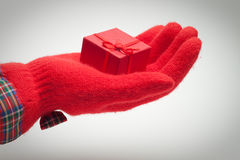 Hand giving present over grey Royalty Free Stock Photography