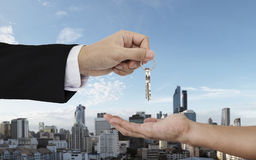 Hand giving and receiving keys with city background, buying home, real estate and house rental concepts. Hand giving and receiving keys with city background Royalty Free Stock Photography