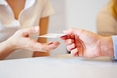 Hand giving smart card to doctors assistant Royalty Free Stock Photography