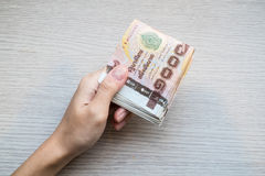 Hand giving stack of thousand bath Thai money Stock Images