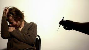 Hand giving syringe to weak-willed female, addiction hopelessness, drugs rehab stock images