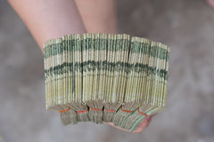 Hand giving Thai banknotes stock photos
