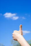 Hand giving thumb up. Against a blue sky Royalty Free Stock Image