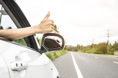 Hand giving a thumbs up sign throw the window of a car parked near the roads.The symbol of a hand raised for help. When the car is broken Royalty Free Stock Photo
