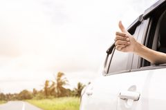 Hand giving a thumbs up sign throw the window of a car parked near the roads.The symbol of a hand raised for help. When the car is broken stock photo