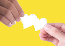 Hand giving white heart. Heart in male and female hands isolated on yellow background Royalty Free Stock Images