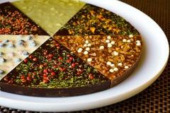 Hand - gjord chokladpizza, blandad vit, mj?lkar och m?rk choklad med olika anstrykningar arkivbild