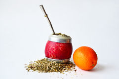 Hand-gjord matt kopp som är full av guarana, det metalliska röret för att dricka och en mandarin Royaltyfri Fotografi