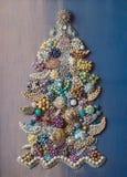 Hand-gjort Dekorativ julgran som g?ras av smycken p? en bl? lutningbakgrund royaltyfri fotografi