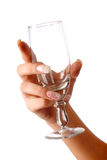 Hand with glass. Close-up hand of a girl is holding empty glass on the white background Royalty Free Stock Images