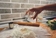 A hand with a glass adds water to the flour. In his hand a glass cup, water pours out of it into a pile of flour for making pizza royalty free stock images