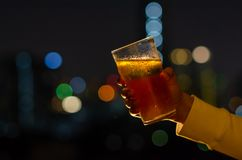 Hand with glass of beer toasting for celebration and party concept isolated on dark night background with colorful city bokeh. Lights on rooftop bar royalty free stock photography