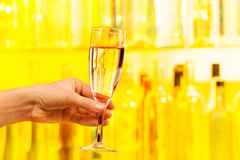 Hand with glass of champagne on yellow background Royalty Free Stock Photo