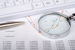 Hand glass on documents with graphs Stock Photography