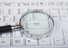 Hand glass on keyboard Royalty Free Stock Images