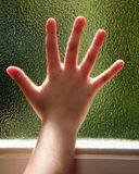 Hand on a glass window. A child's hand silhouetted by the sun against a frosted glass window Royalty Free Stock Photography